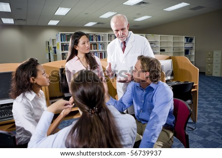 Multiracial university students with professor conversing in library - stock photo