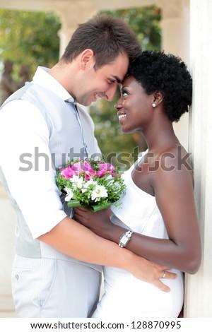 Multiracial wedding couple posing outdoors - stock photo