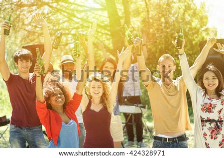 Multiracial young friends dancing in garden party with deejay in background - Cheerful people holding bottle beers on barbecue weekend day - Friendship and joyful concept - Soft vintage filter  - stock photo
