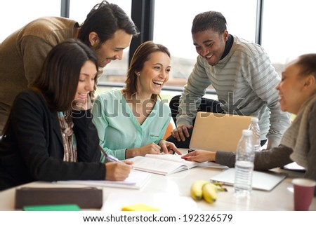 Multiracial young people enjoying group study at table. Happy university students sitting together at table with books and laptop for researching information for their project. - stock photo
