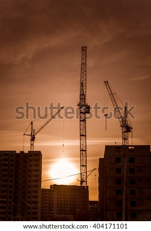 Multistorey houses under construction and crane/Modern buildings under construction and tall cranes