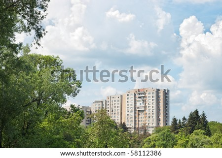 multistoried apartment building with trees against blue sky and white clouds - stock photo