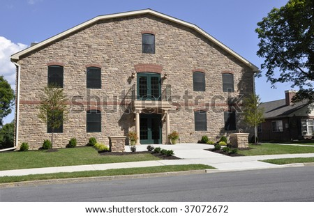 multistory stone office building by a street and sidewalk - stock photo