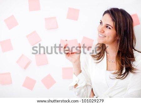 Multitask business woman with post-its and smiling - stock photo