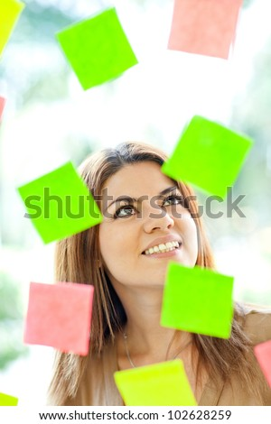 Multitask woman with post-its all around and smiling - stock photo