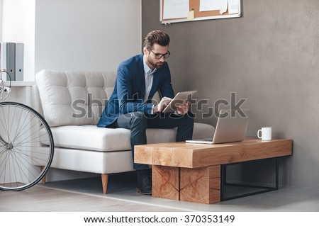 Multitasking. Handsome young man wearing glasses and working with touchpad while sitting on the couch in office - stock photo