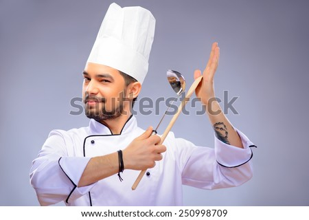 Multitasking is a chefs game. Closeup portrait of handsome cook holding a wooden culinary spoon and soup ladle and winking to camera while standing over grey background with copy space - stock photo