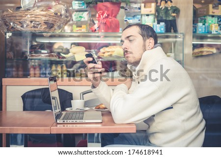 multitasking man using tablet, laptop and cellphone connecting wifi - stock photo