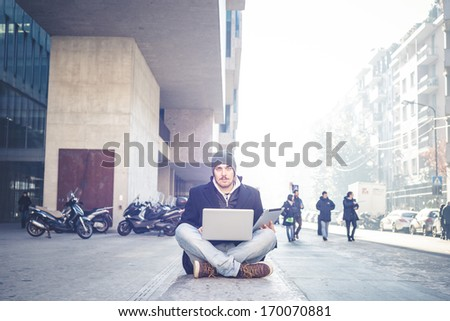 multitasking man using tablet, laptop and cellphone connecting wifi in the city street urban - stock photo