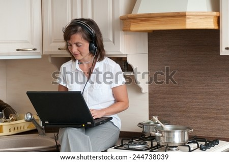 Multitasking - preparing meal and working - stock photo