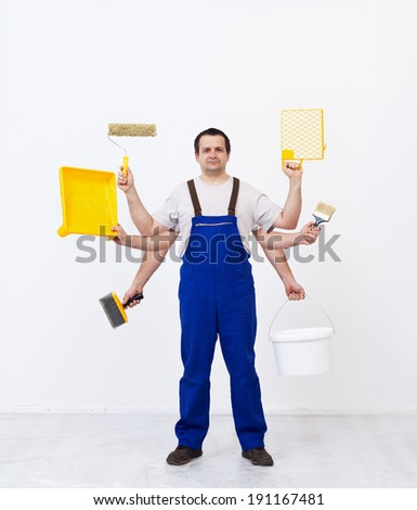 Multitasking worker ready to paint the room - holding painting utensils - stock photo