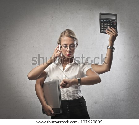 Multitasking young businesswoman doing many things at the same time - stock photo