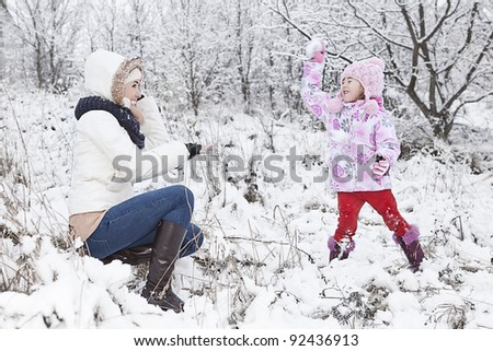 mum and daughter having fun on the snow - stock photo