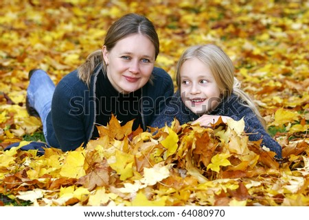 Mum and daughter in pile of autumn leaves - stock photo