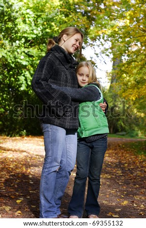 Mum and daughter in the autumn park - stock photo