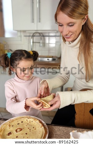 Mum and daughter making pancakes - stock photo