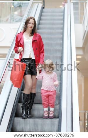 Mum and daughter on the escalator - stock photo
