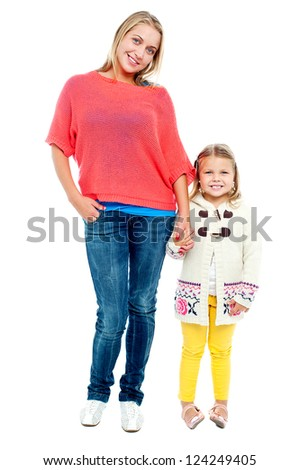Mum and daughter posing in trendy outfits. Full length portrait - stock photo