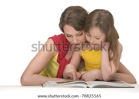 Mum and daughter sit at table and read book - stock photo