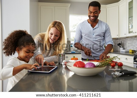 Mum and daughter use tablet computer, and dad prepares food - stock photo