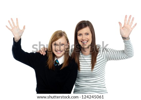 Mum and daughter waving hands at the camera. Having fun together. - stock photo
