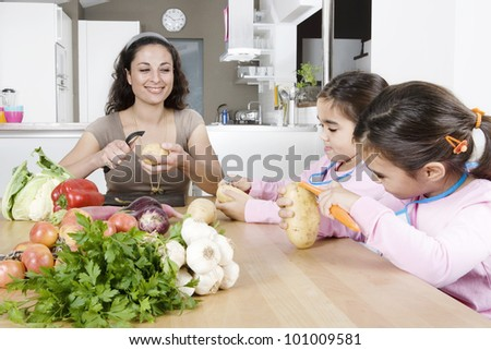 Mum and daughters peeling potatoes at a kitchen's table.