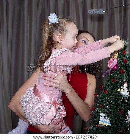 Mum and her small daughter decorate a christmas fur-tree