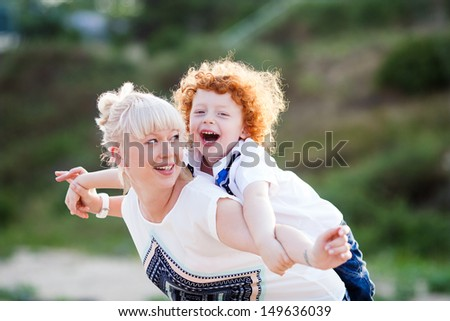 mum and son having fun outside, making plane figure and laughing - stock photo