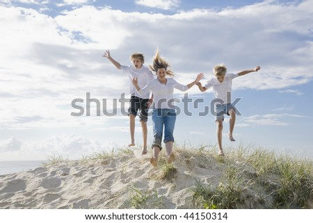 Mum and sons jumping of a sand dune at the beach - stock photo