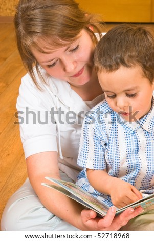 Mum and the son look the book