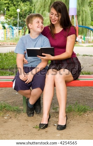 Mum and the son reads the book in park