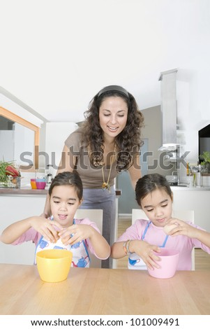Mum and twin daughters cracking eggs open into bowls in the kitchen. - stock photo