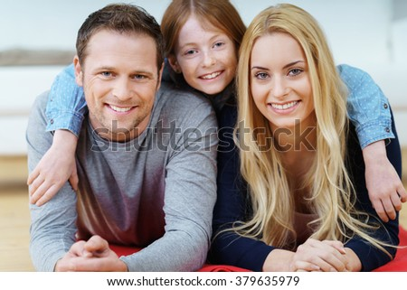 Mum, Dad and their cute young daughter relaxing together on a rug on the floor facing towards the camera with happy friendly smiles