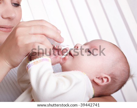 Mum digs in a medicine in a nose to the child - stock photo