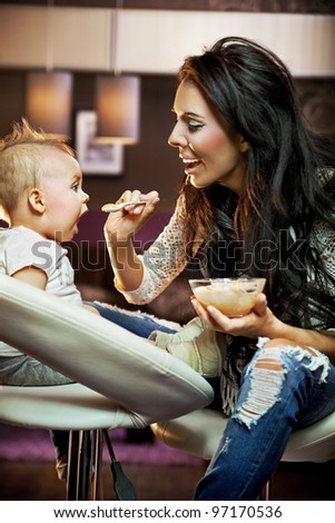 Mum feeding her baby - stock photo