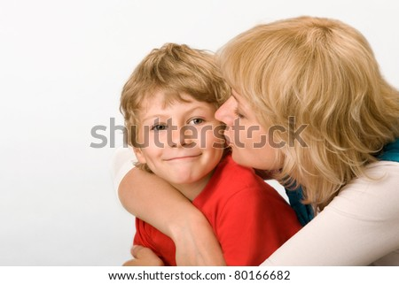 Mum gently kisses the son - stock photo
