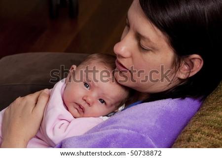 mum giving her newborn baby a hug - stock photo