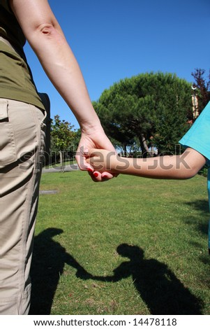 Mum holding the hand of her son on a park with shadow - stock photo
