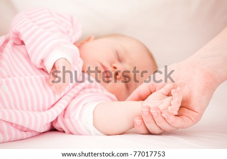 Mum holds by the hand the sleeping baby. - stock photo