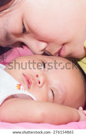 Mum kiss with his baby girl. - stock photo