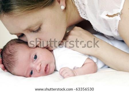 Mum kissing her baby - stock photo