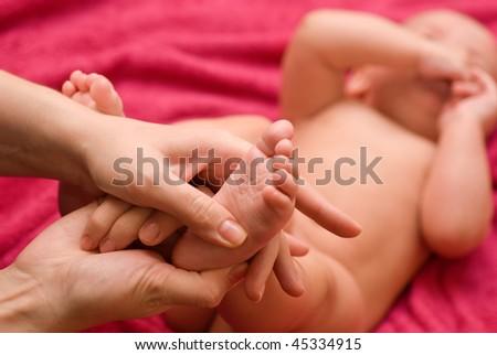 Mum massaging her baby's foot shallow focus - stock photo