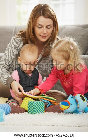 Mum playing on floor with two children at home. - stock photo