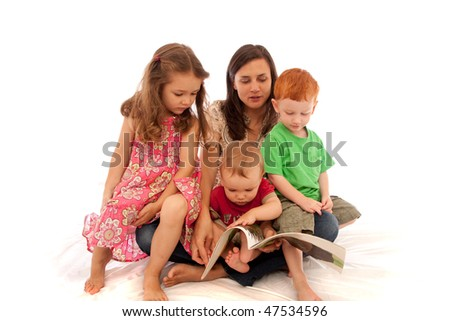 Mum reading to three young kids on her lap - stock photo