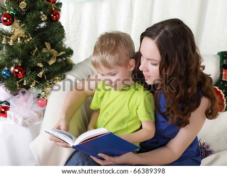Mum reads to the son the book near a christmas fur-tree - stock photo
