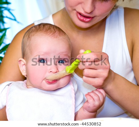 Mum spoon-feeds the child in house interior