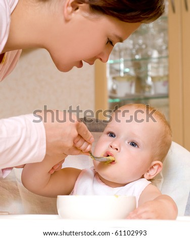 Mum spoon-feeds the child in house interior - stock photo