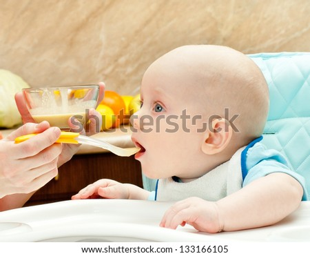 Mum spoon-feeds the child in the kitchen - stock photo