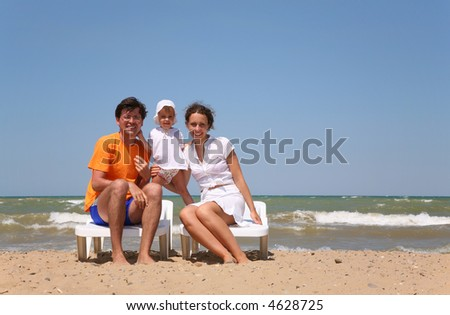 Mum, the daddy and the child sit on chairs near the sea.