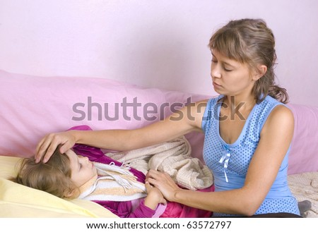 Mum touches a forehead at the sick child